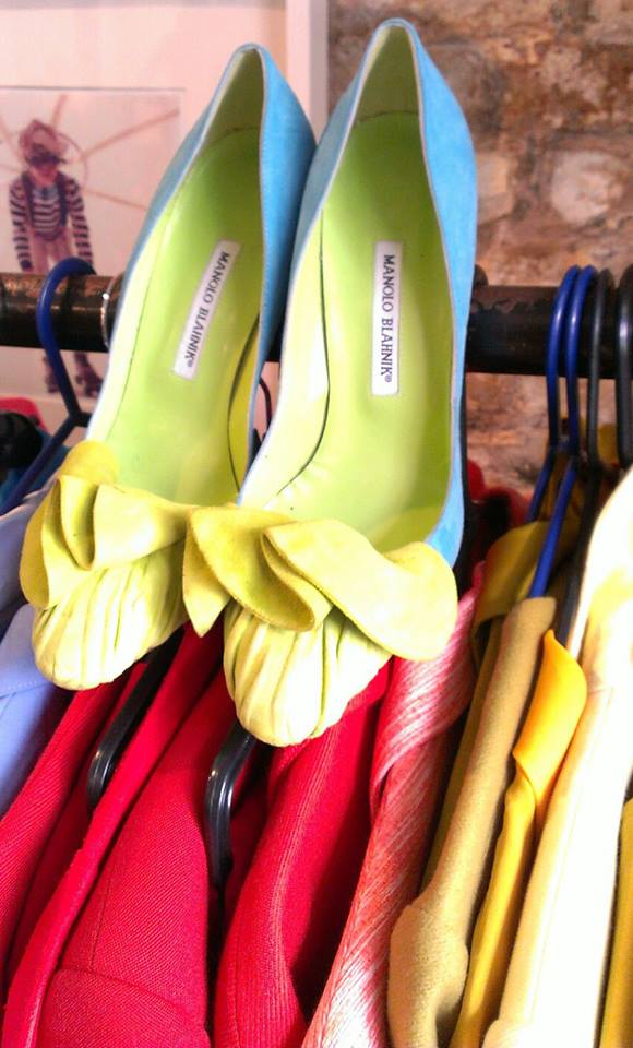 An image of new yellow, green and blue Manolo Blahnik shoes on top of a rail of colourful assorted clothes